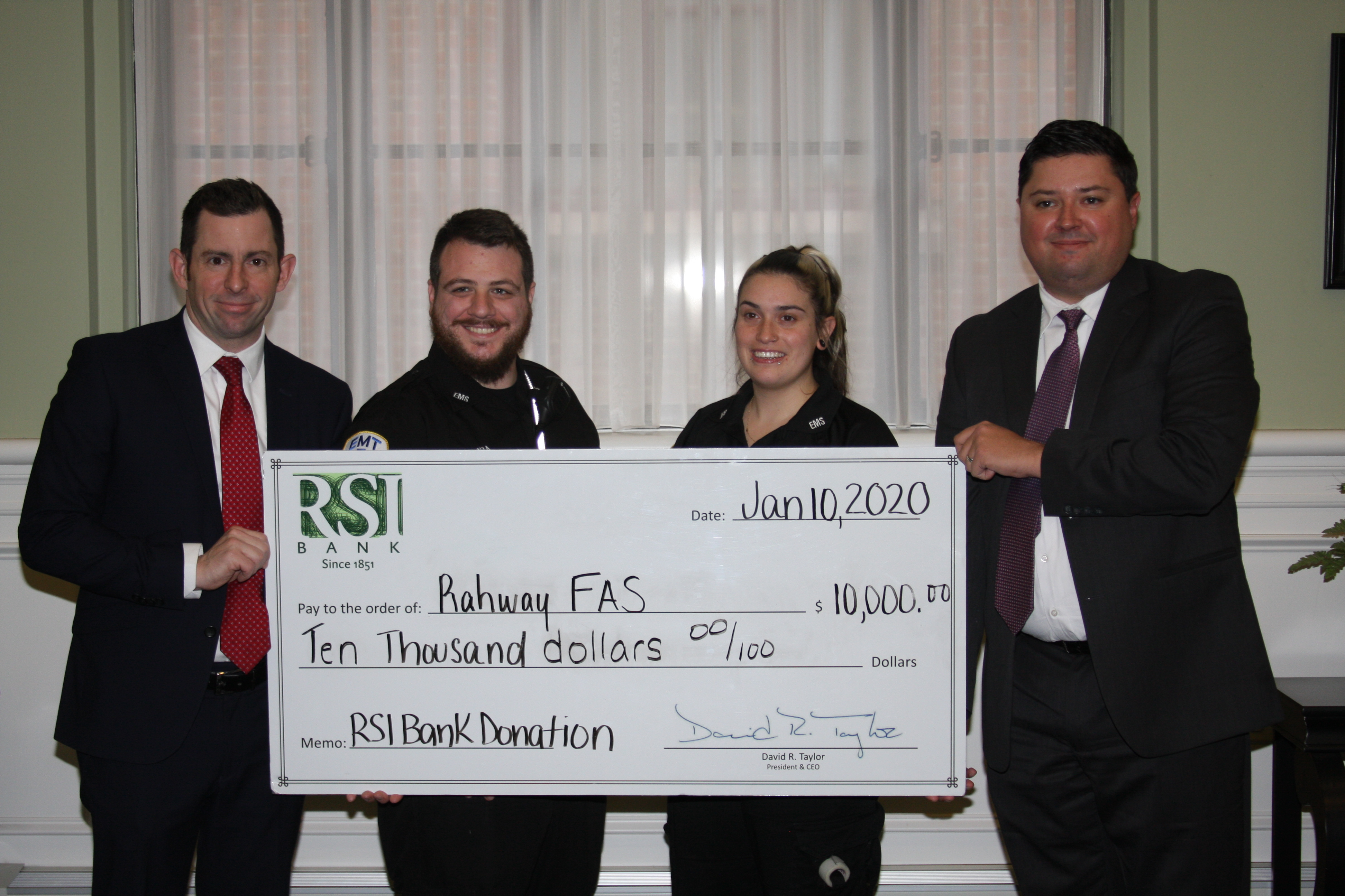 Rahway First Aid Squad accepts a check from RSI Bank in the amount of $10,000.