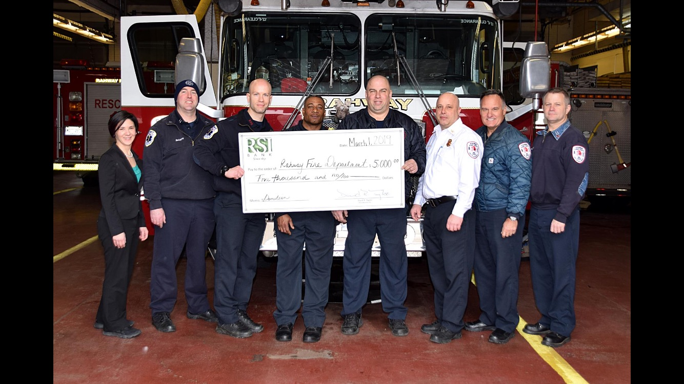 A bank representative stands next to 7 firemen in front of a fire truck. The firemen are holding a check for $5,000.
