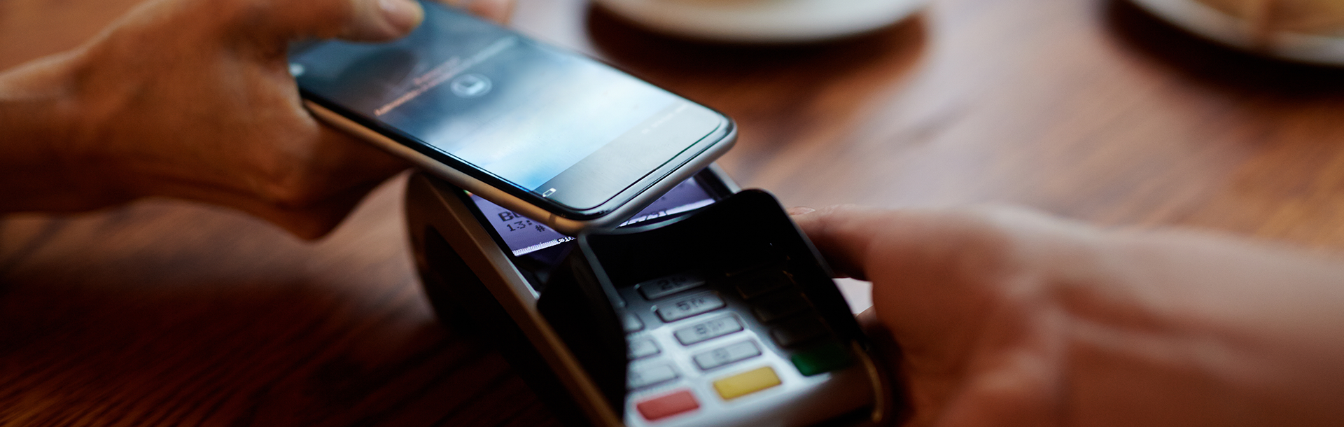 A customer uses their mobile phone to make a payment in a cafe