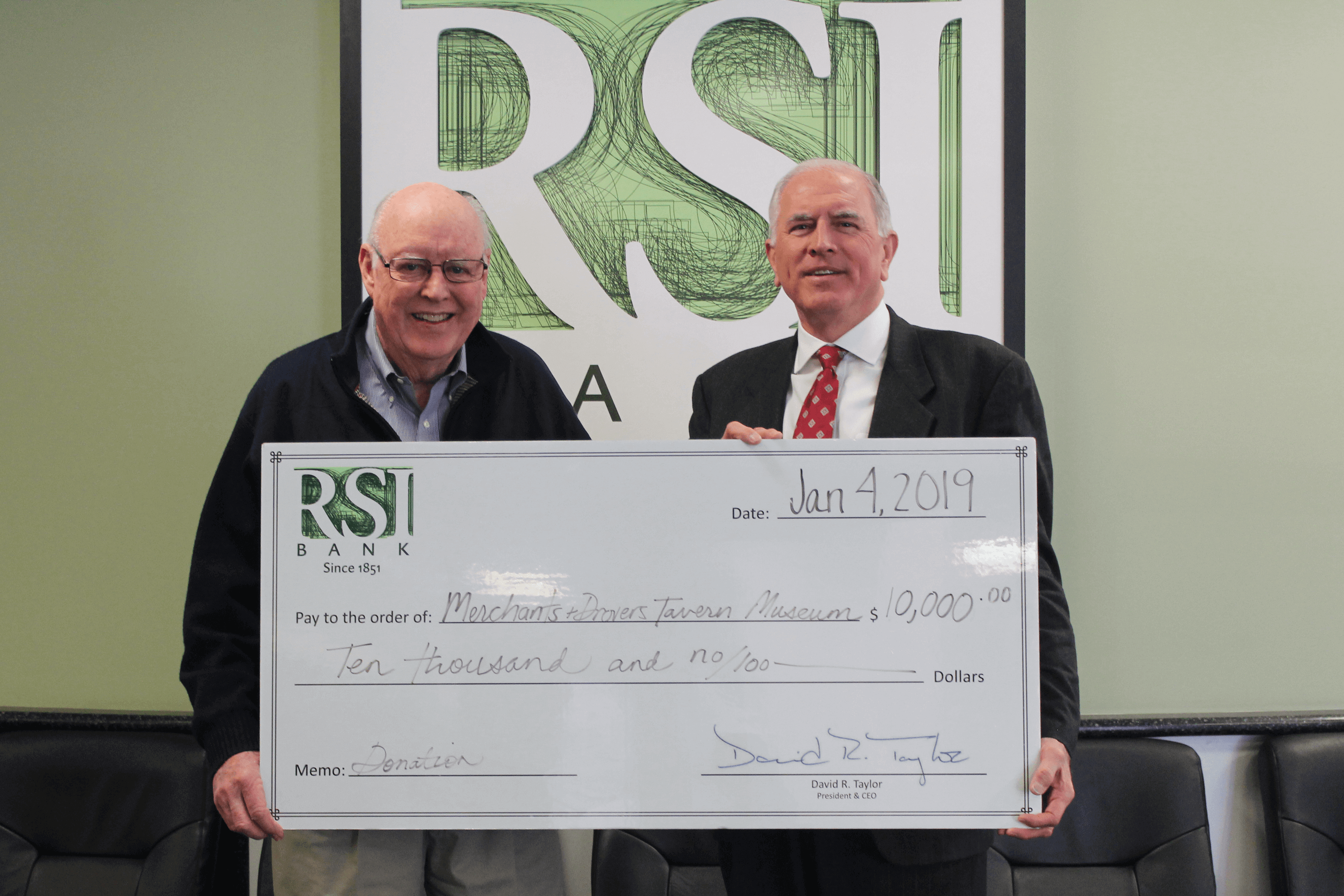 David R. Taylor, Chairman, CEO and President of RSI Bank, presents a donation check to Alex Shipley, Director of Museum Operations. The men are standing in front of the RSI Bank logo sign in the bank lobby.