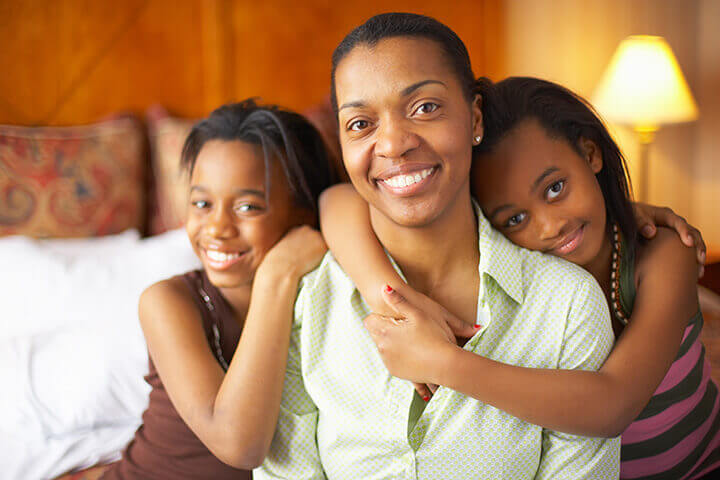 A smiling woman is being hugged by her two daughters, while sitting on her bed.